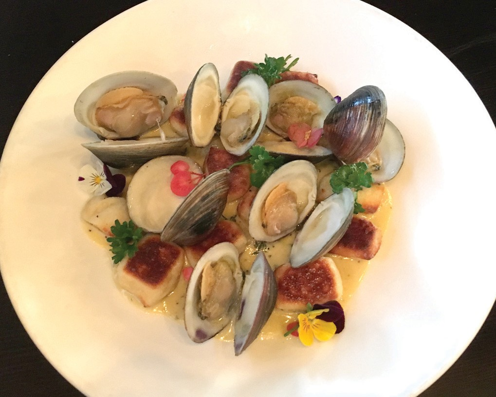 Crispy browned gnocchi, above, are nestled among plump clams in creamy sauce. Smoked grilled octopus, above right, arrives under a glass dome filled with smoke. Chocolate Meltdown, right, is a lava cake filled with berry jam and topped with ice cream.