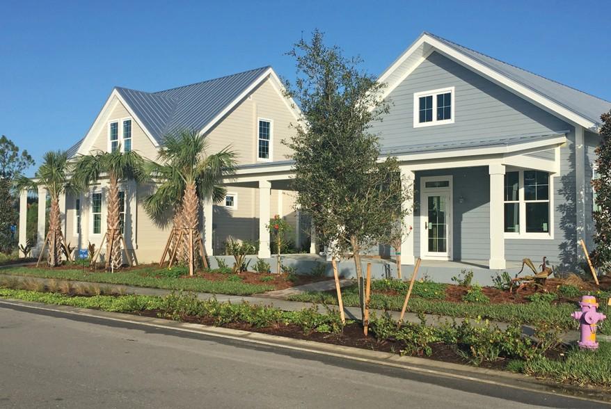 Model homes along a palm-tree lined street