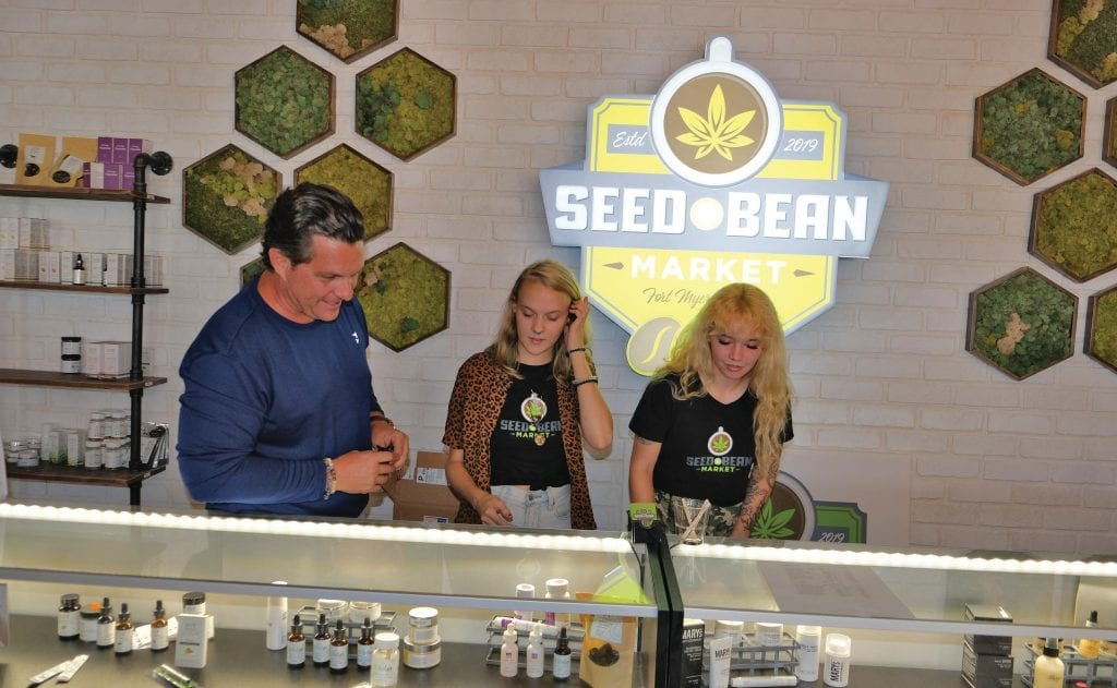 Seed & Bean Market is a cannabis café and lifestyle shop in the Fort Myers River District owned by Cole Peacock, at left. He is pictured here with store associates Natasha Lehtola and Kimberly Victor. EVAN WILLIAMS / COURTESY PHOTO