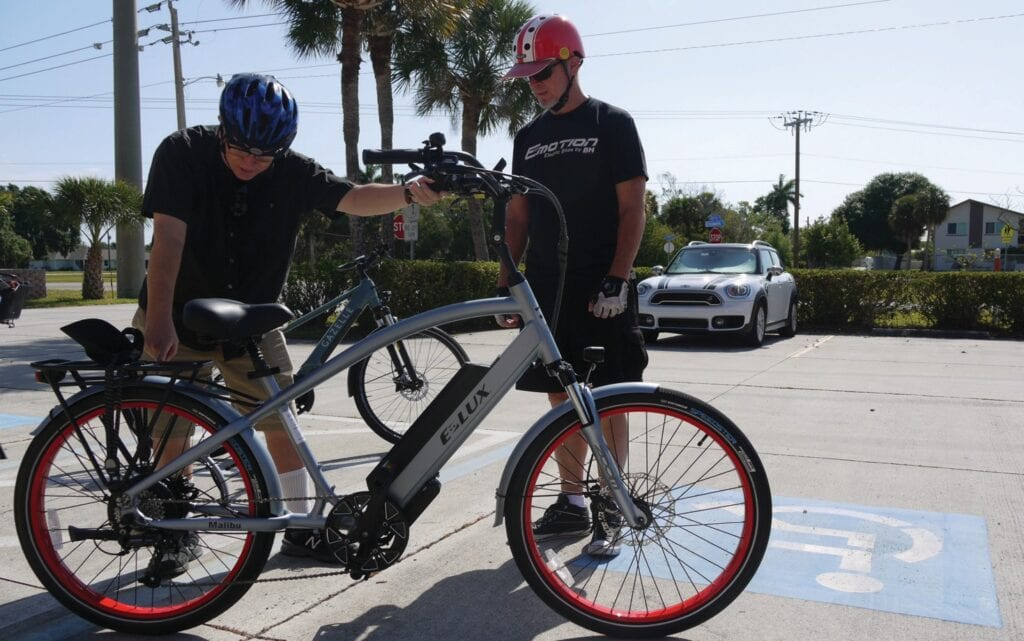 Philipp Pfaeffli (in the red helmet), the owner of PedelecSQB Electric Bicycle Shop in Punta Gorda, shows a potential customer the features of a pedal-assist electric bicycle. LAURA TICHY / FLORIDA WEEKLY